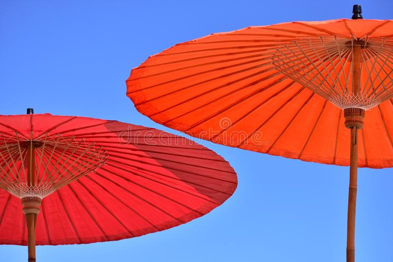 Close-up of a red and orange parasol umbrella against the blue sky stock photography