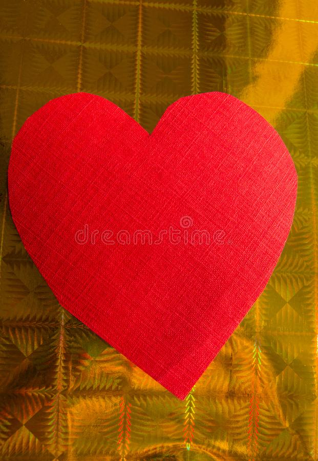 Close-up of red paper heart on gold holographic wrapping paper background, vertical photo, copy space royalty free stock photo