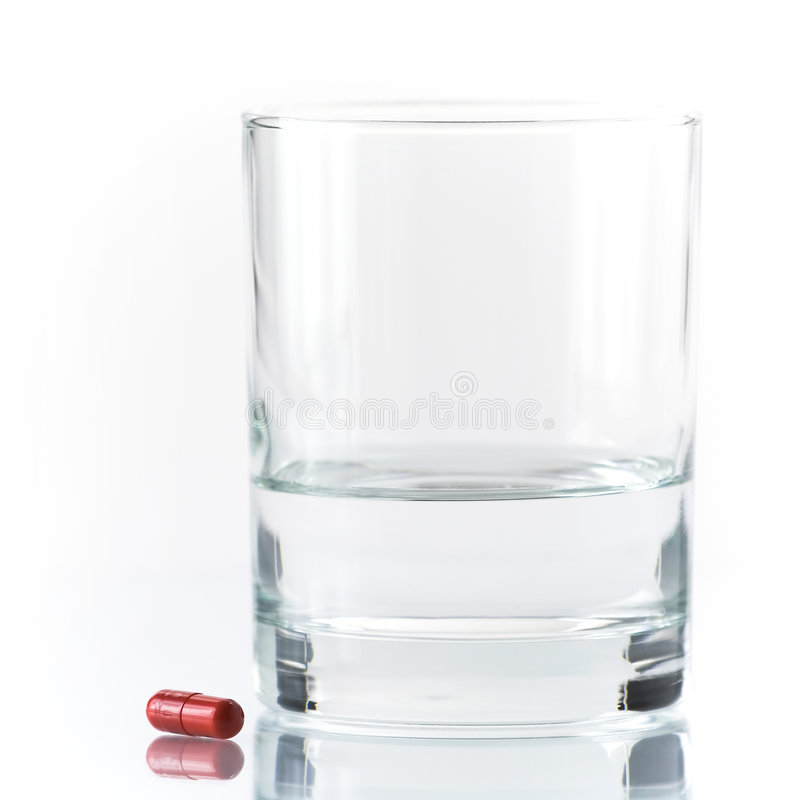 Close up of red pill and water royalty free stock photography
