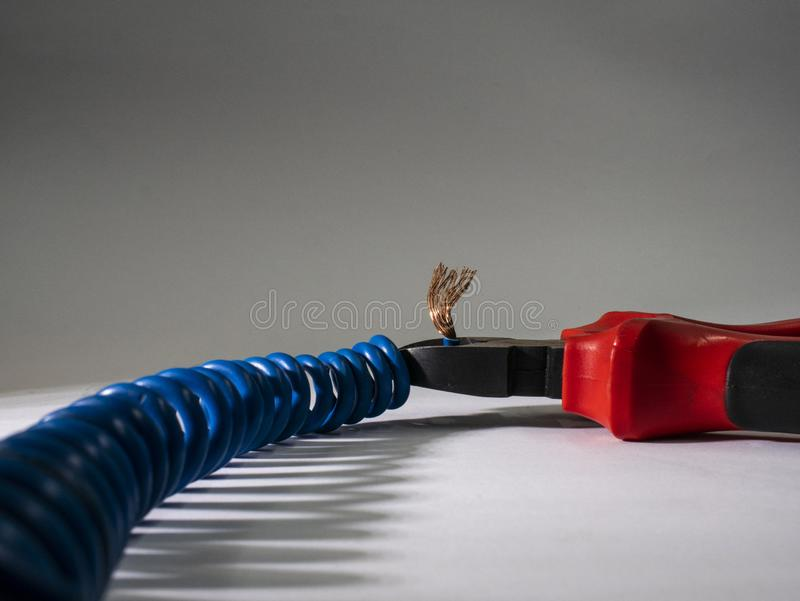 Close up of red pliers and blue twisted wire on white background.Pliers cutting cable stock photo