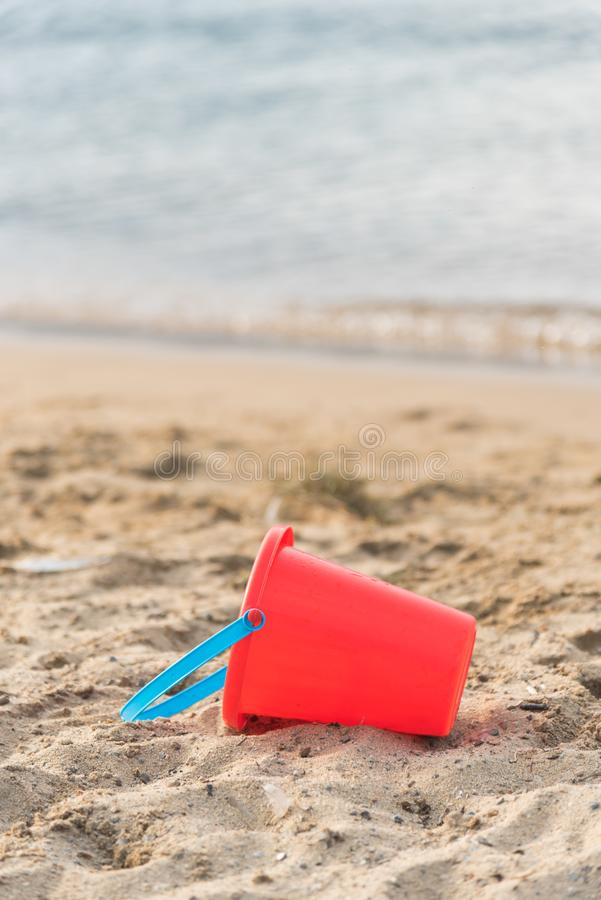 Child`s red sand pail lying on sandy beach with water in background. Close-up of red sand pail with blue handle lying on sandy beach in sunshine with water in stock photos
