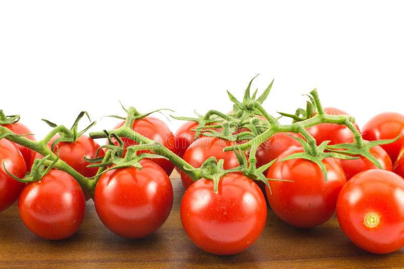 Close up of red small cherry tomatoes on a wooden surface and white background.  royalty free stock photography