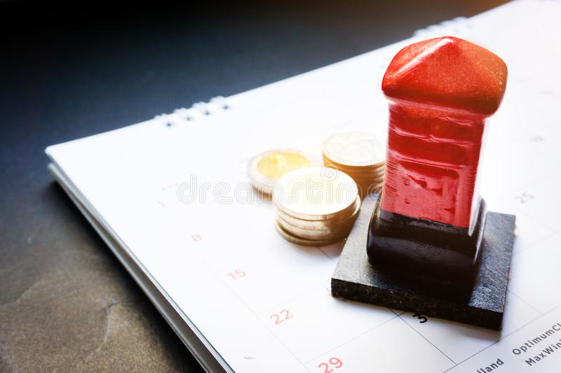 Close up red toy post box and money baht coin on the monthly planner calendar on black background. Summer calendar schedule. Calen royalty free stock images