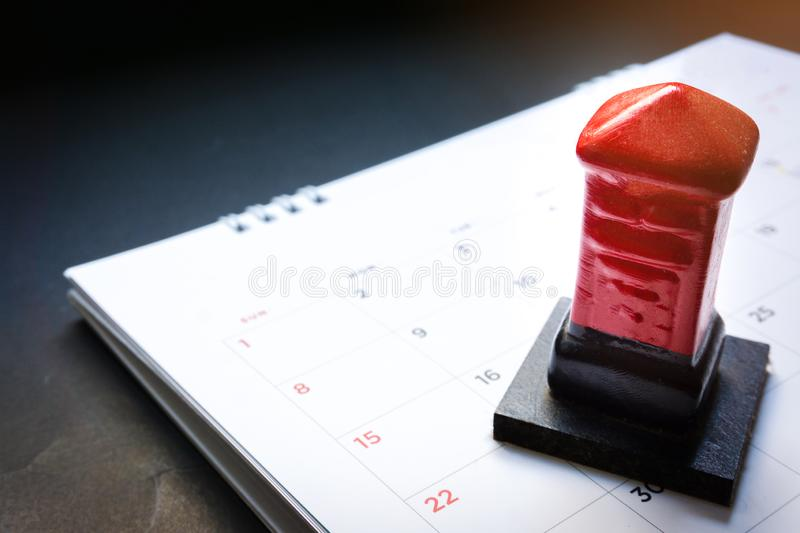 Close up red toy post box on the monthly planner calendar on black background. Summer calendar schedule. Calendar scheduling for t royalty free stock photo
