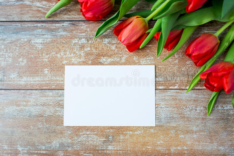Close up of red tulips and blank paper or letter. Advertisement, valentines day, greeting and holidays concept - close up of red tulips and blank paper or letter stock photo