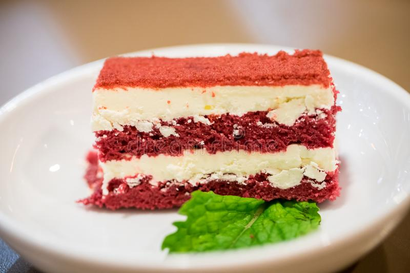 Close up red velvet cake in the white dish with peppermint leaf. i royalty free stock images