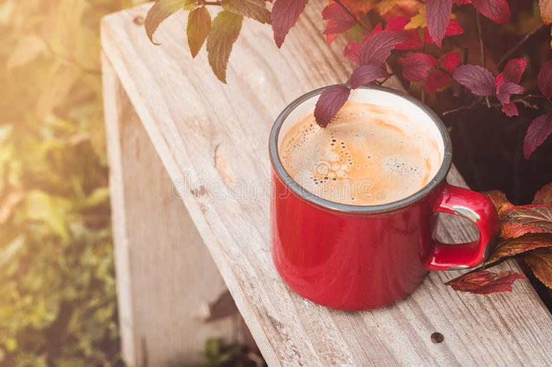 Close up red vintage coffee cup on wooden background in garden with blur light bokeh and autumn leaves royalty free stock photo