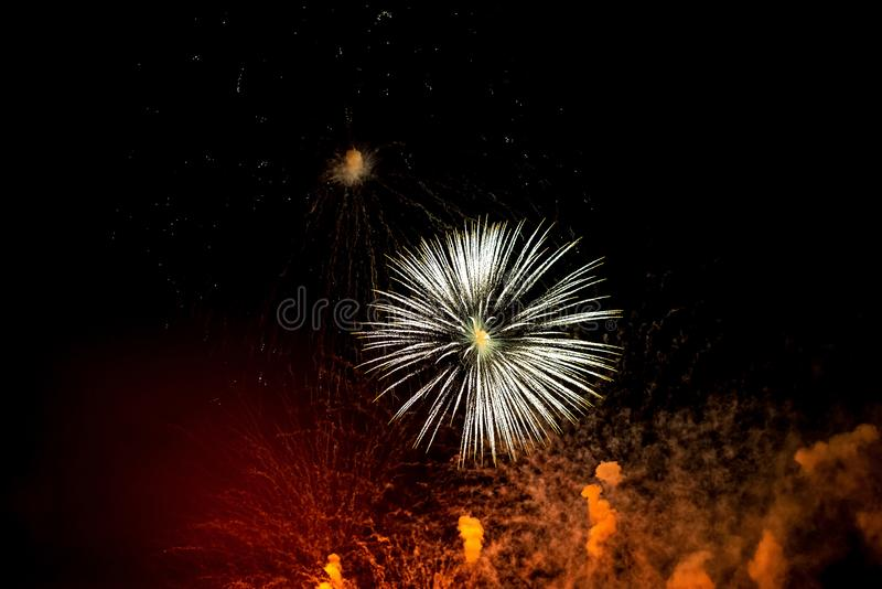 Close-up red and white festive fireworks on black background. Abstract holiday background stock photography