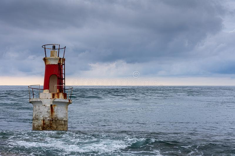 Close-up of red and white lighthouse at high tide on a cloudy afternoon royalty free stock images