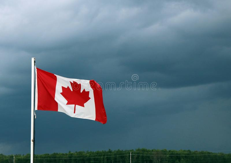 Canadian Flag Waves Ahead of Dark Storm Clouds royalty free stock photos