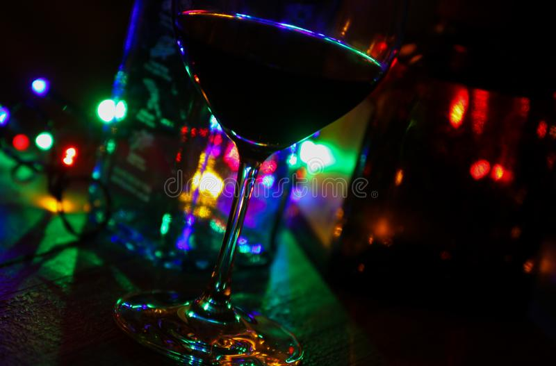 Close up of red wine glass with bottles of alcohol and colorful electric light royalty free stock images