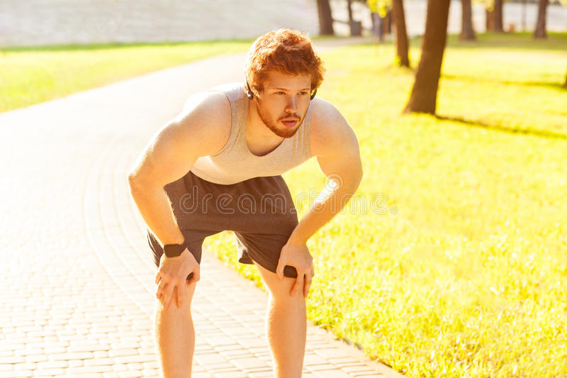 Close up. Redhead young adult man tired after running. stock photos