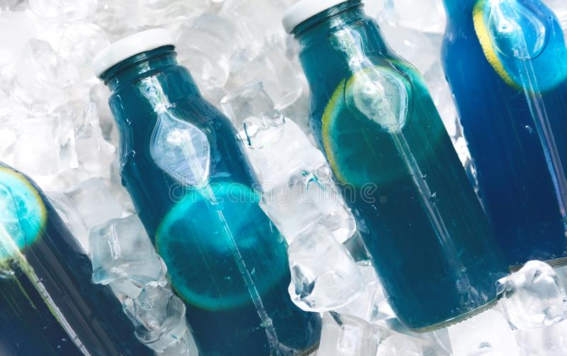 Close up of refreshing blue detox water with lemon in glass jar. On ice background, panorama stock photography