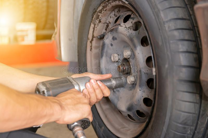 Close up of repair mechanic hands during maintenance work to pneumatic gun to loosen a wheel nut changing tyre of car stock photography