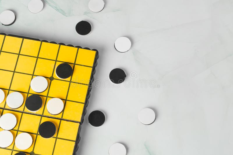Close-up Reversi or Othello strategy board game with black and white disks. stock photography