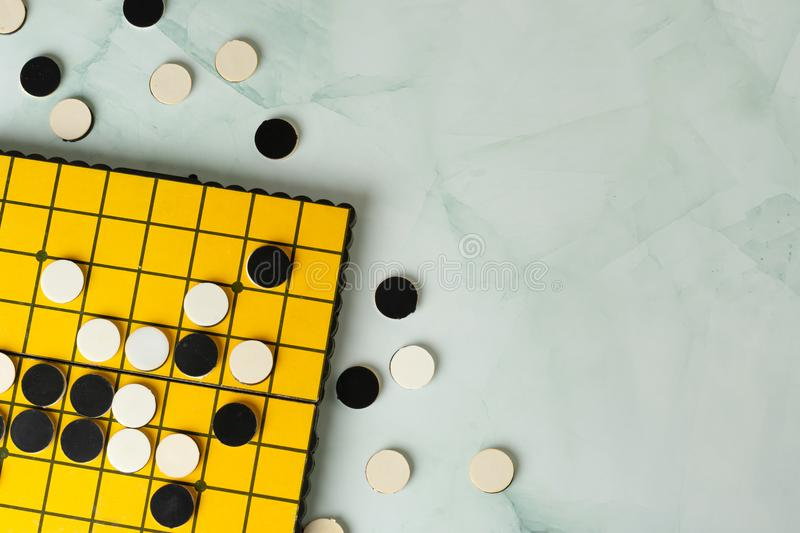 Close-up Reversi or Othello strategy board game with black and white disks. stock photos