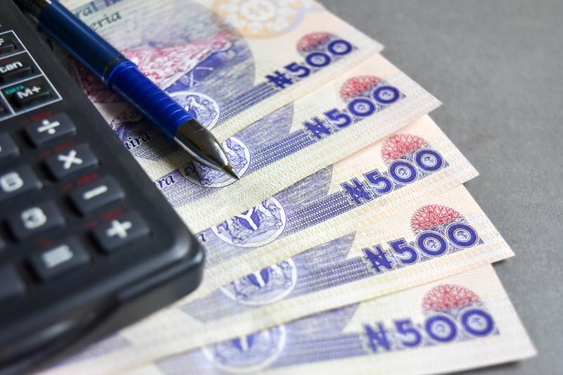 Close up of rice with Nigerian five hundred naira notes wit pen and calculator. For finance, investment and growth concept for banking background royalty free stock images