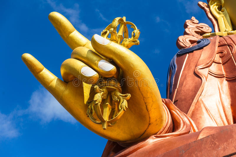Close up at the right golden hand with mace of Guru Rinpoche statue, the patron saint of Sikkim in Guru Rinpoche Temple at Namchi. Sikkim, India royalty free stock image