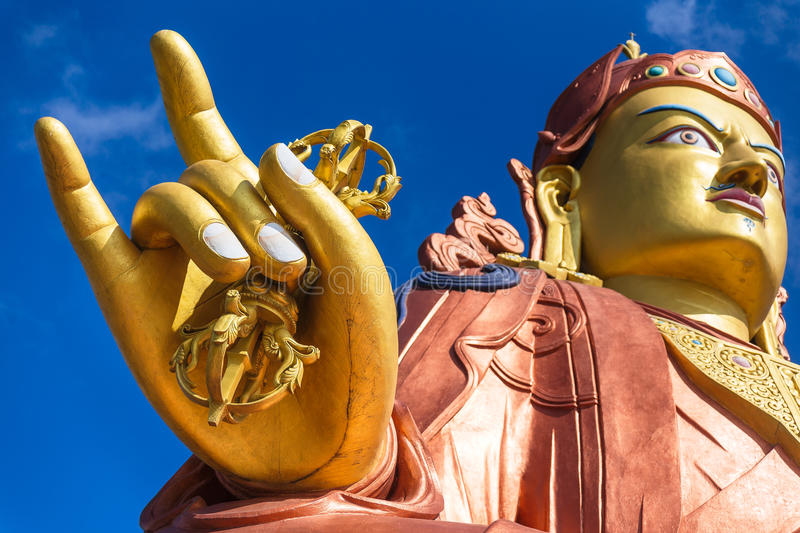 Close up at the right golden hand with mace and head of Guru Rinpoche statue, the patron saint of Sikkim in Guru Rinpoche Temple. Close up at the right golden royalty free stock photo