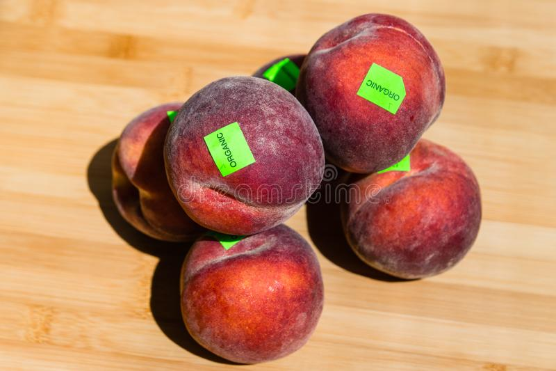 Close up of ripe peaches, carrying organic stickers, on a wooden board background stock images