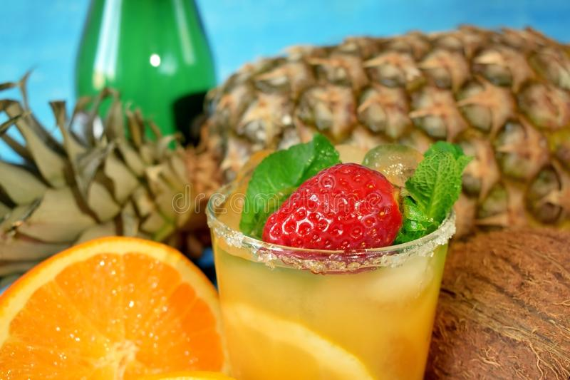 Close-up of a ripe strawberry and mint in the glass with orange drink royalty free stock photos
