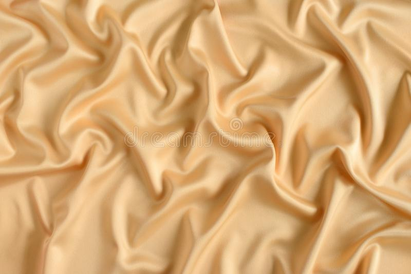 Close up of ripples in gold colored silk fabric. Satin textile background. Close up of ripples in gold colored silk fabric royalty free stock photography