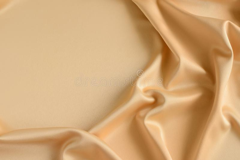 Close up of ripples in gold colored silk fabric. Satin textile background. Free copy space. Close up of ripples in gold colored silk fabric. Satin textile royalty free stock photography
