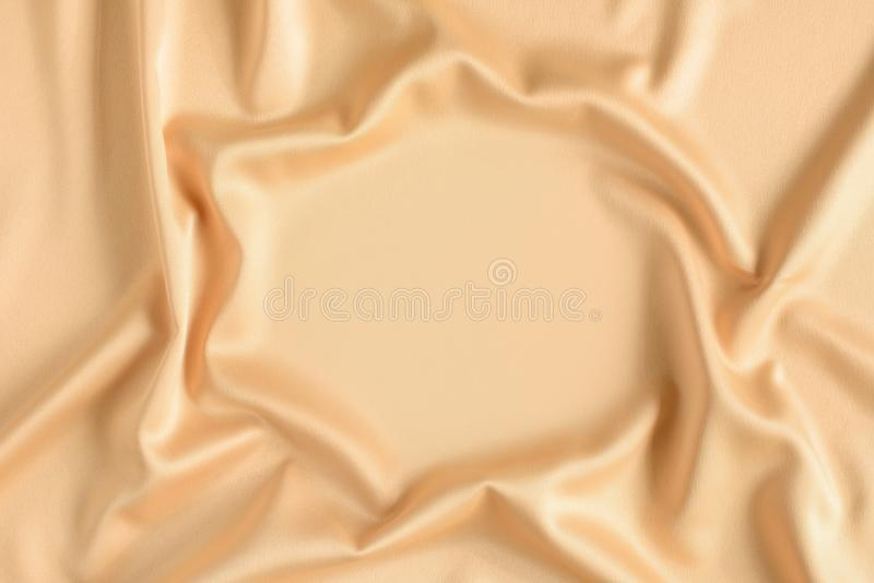 Close up of ripples in gold colored silk fabric in shape of frame. Satin textile background. Free copy space. Close up of ripples in gold colored silk fabric in stock images