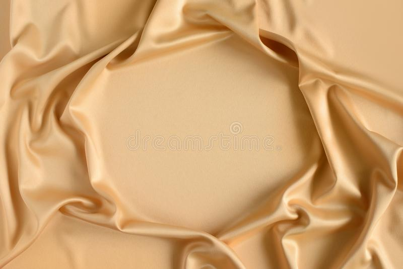 Close up of ripples in gold colored silk fabric in shape of frame. Satin textile background. Free copy space. Close up of ripples in gold colored silk fabric in royalty free stock image
