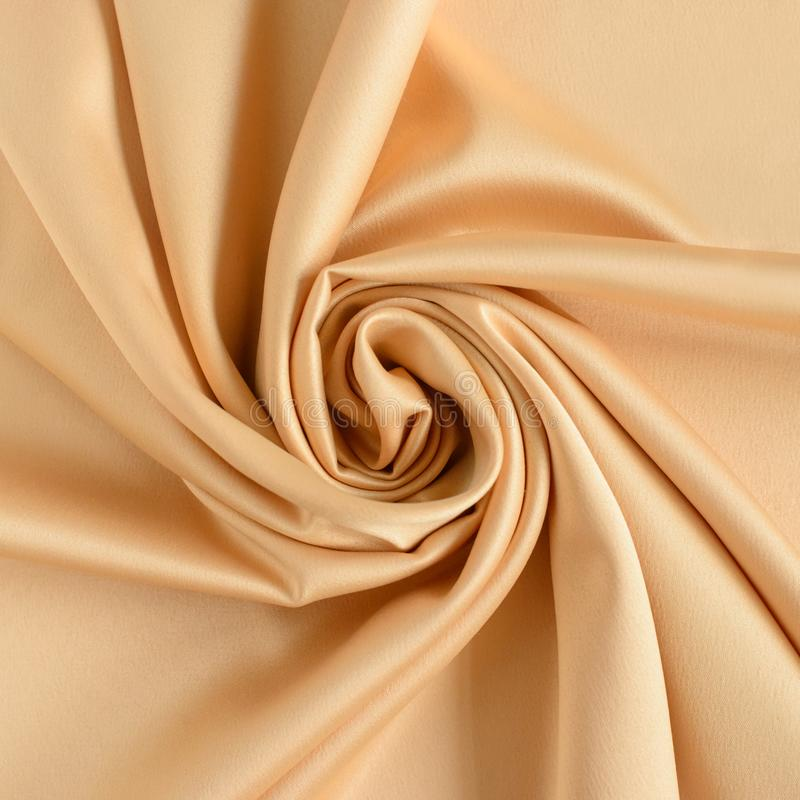Close up of ripples in shape of rose flower in gold colored silk fabric. Satin textile background. Close up of ripples in shape of rose flower in gold colored stock photos