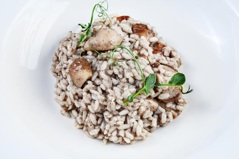 Close up risotto with porcini mushrooms and truffle pasta in white bowl. Homemade italian cuisine. Healthy food with copy space. royalty free stock image