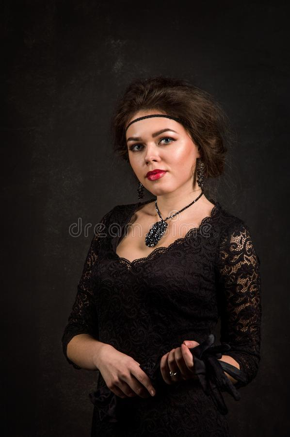 Close up. Roaring Twenties. Woman portrait in the style of Gatsby. Low key. A beautiful young woman in a black dress. royalty free stock image