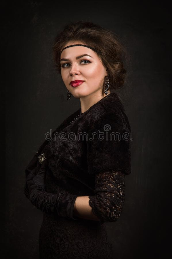 Close up. Roaring Twenties. Woman portrait in the style of Gatsby. Low key. Beautiful young woman in a black dress, satin gloves. stock images