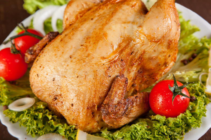 Close-up of roast chicken with fresh vegetables royalty free stock photography
