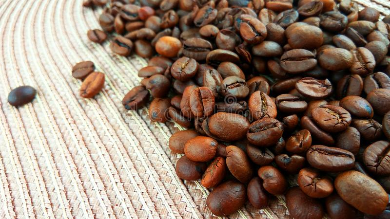 Roasted brown coffee beans on light textile cloth background. Close up roasted brown coffee beans on light textile cloth background stock photography