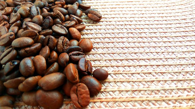 Roasted brown coffee beans on light textile cloth background. Close up roasted brown coffee beans on light textile cloth background stock images
