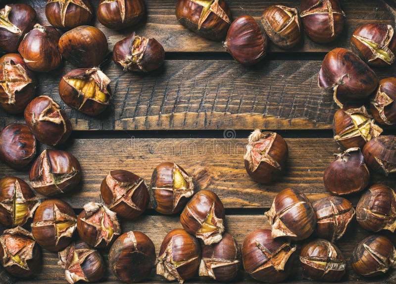 Close-up of roasted chestnuts over rustic wooden background stock photography