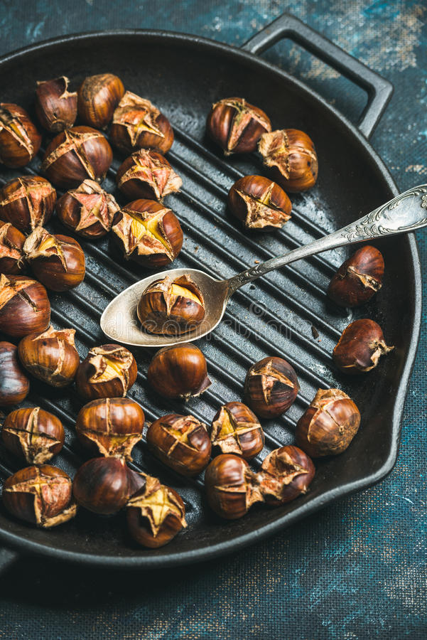 Close-up of roasted chestnuts and spoon in grilling pan stock photo