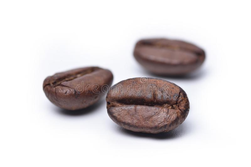 Roasted coffee beans isolated on white background. Close up roasted coffee beans isolated on white background, selective focus stock image