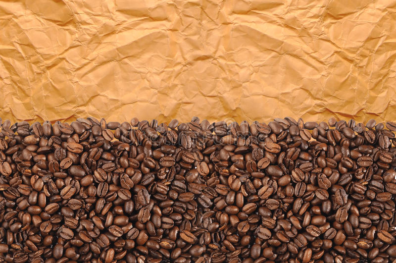 Close-up of roasted coffee beans over old yellow paper royalty free stock photography