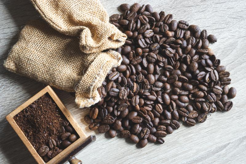Close up Roasted coffee beans with small sack and crushed bean. On wood background royalty free stock image