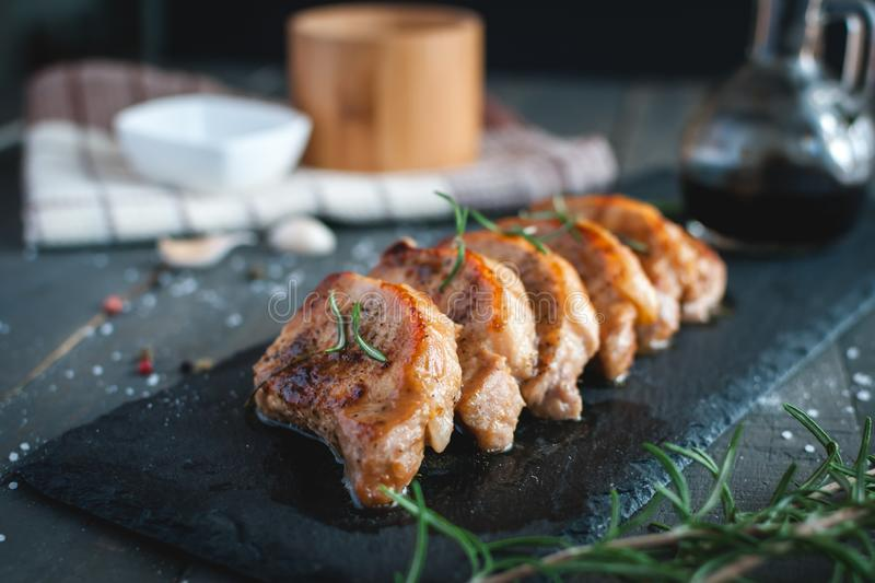 Close-up of roasted pork chops with fresh rosemary on dark background. Close-up of roasted pork chops with fresh rosemary, sea salt, pepper and gravy, on dark stock images