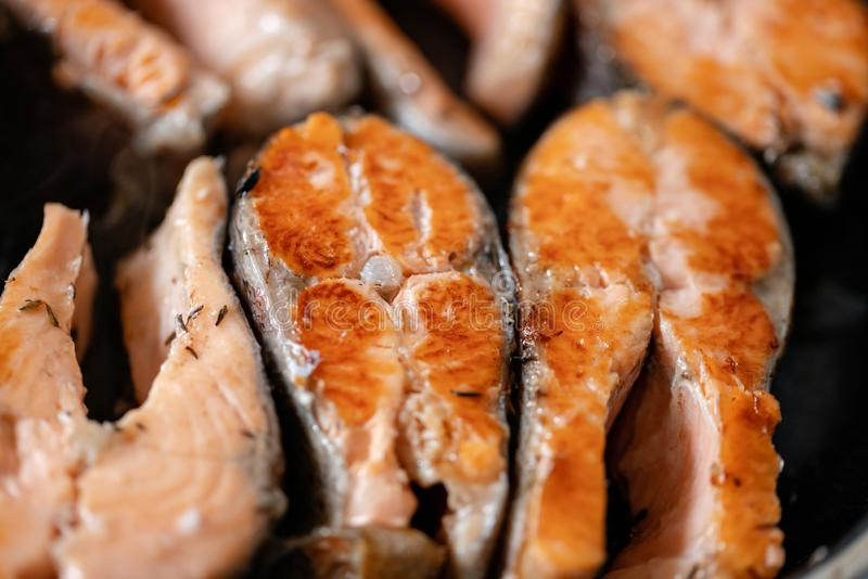 Close-up of roasted salmon steaks in a frying pan, top view. Fresh seafood for frying. royalty free stock photography