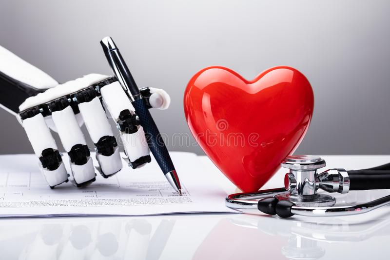 Close-up Of A Robot Filling Document. With Stethoscope And Heart On Desk royalty free stock photo