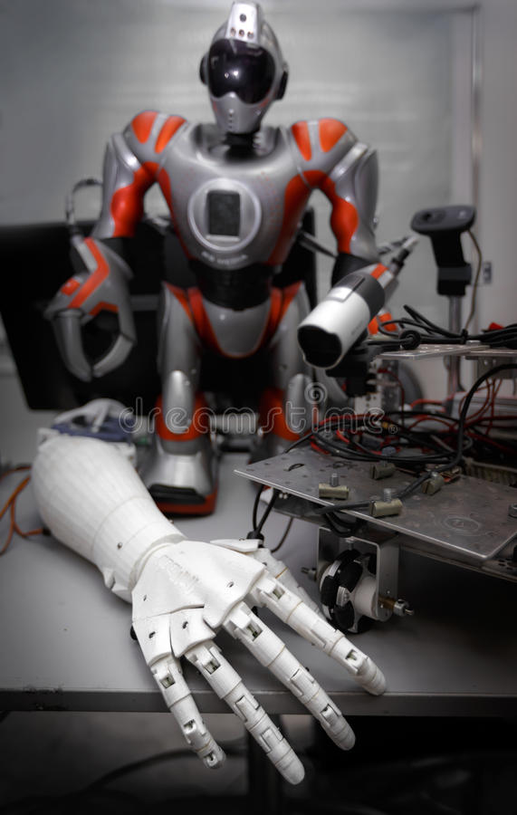 Close up of robot hand on table with another robot and details at background. Concept of future technology stock photo