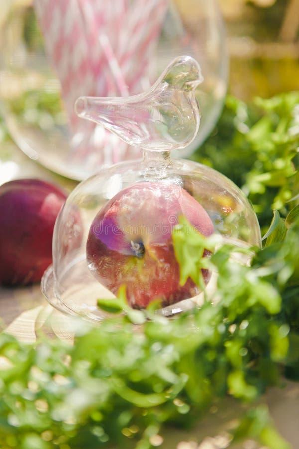 Close-up rode appel in een glaskruik met een deksel met een vogel, de decoratie van de huwelijkspicknick, selectieve nadruk royalty-vrije stock foto