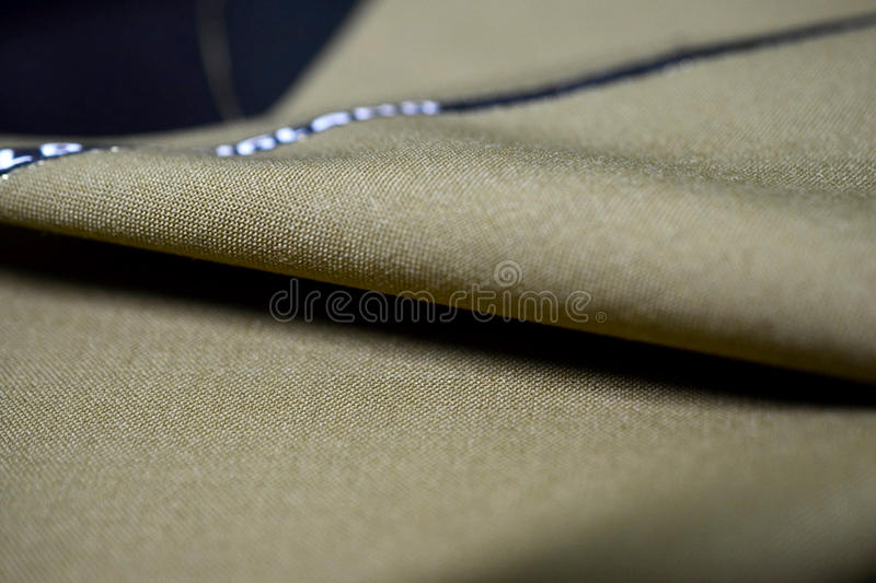 Close up roll texture light brown gold fabric of suit. Photo shoot by depth of field for object stock photo