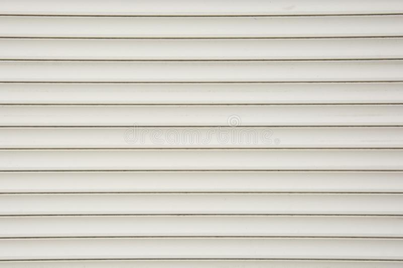 Close up of a roller shutter door, plastic white texture background royalty free stock photography