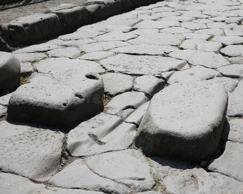 Close up of Roman Road at the ruins of Pompeii Italy. Roman road at the ruins of Pompeii destroyed by volcanic eruption of Vesuvius in AD 79 royalty free stock image