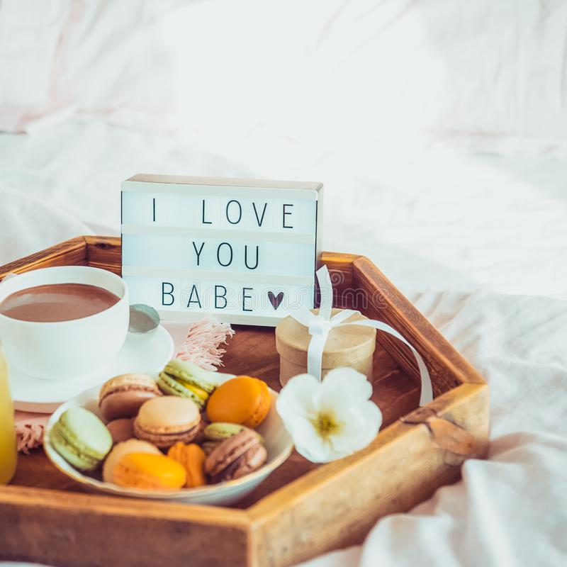 Close up Romantic Breakfast in bed with I love you baby text on lighted box. Cup of coffee, juice, macaroons, flower and gift box. On wooden tray. Birthday stock photography